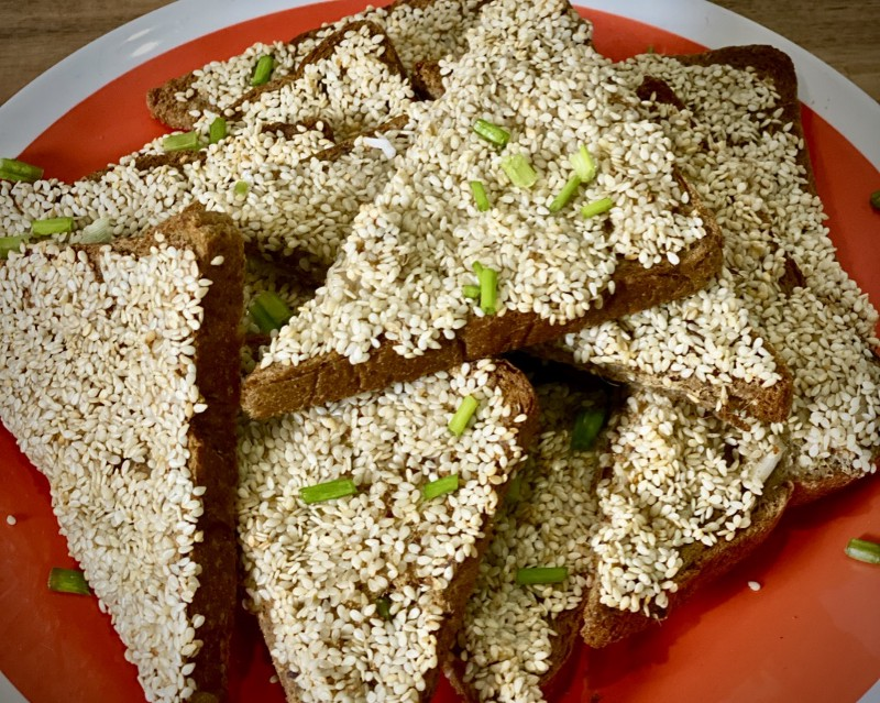A pile of sesame toast triangles covered in white sesame seeds, on a red plate
